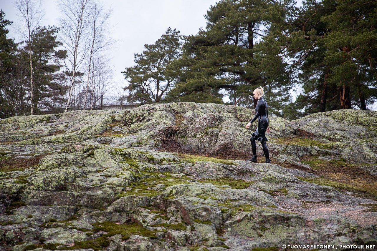 A woman walks up a rocky hill wearing a latex catsuit and a latex dress.